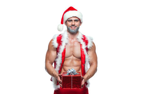 Sexy Santa Claus. Bodybuilder young handsome santa clause smile holds a gift in a red box and shows off abs cubes at New Years eve and Christmas winter holiday white background.