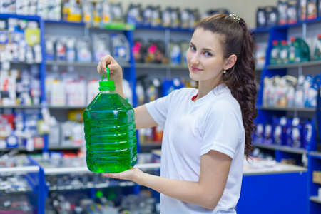 Young girl saleswoman offers a bottle of non-freezing cleaning liquid for washing the windshield of a car in an auto parts store