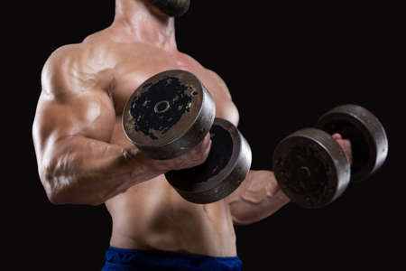 Close up of muscular sportsman lifting heavy dumbbells showing his strong biceps isolated on black backgrounds