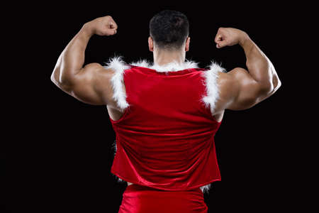 Back view of young Santa Claus showing off his strong biceps isolated on black background