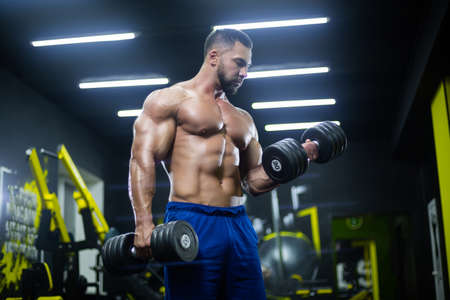 Front view of a muscular bodybuilder lifting dumbbells in blue shorts posing in a gym 免版税图像 - 157887946