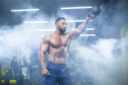 Portrait of a muscular sportsman performing kettlebell swings with one hand in a gym standing in smoke