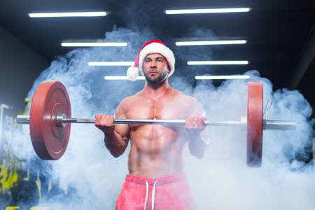 Front view of a sexy muscular man wearing Christmas hat and red shorts lifting a barbell in a gym standing in smoke