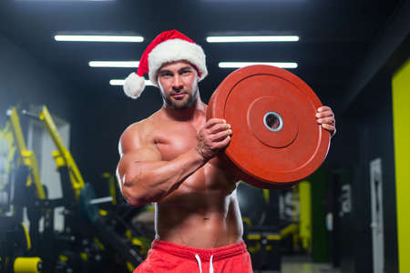 Young strong muscular Santa Claus in a red hat and shorts is looking at camera lifting a heavy disc in a gym