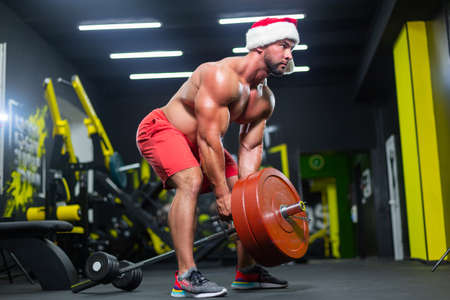 Muscular Santa Claus in wearing christmas hat and red shorts is lifting a barbell from the floor in a gym performing a workout 免版税图像 - 157887951