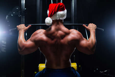Handsome fitness man in Christmas hat is performing back workouts using thrust of the upper block machine in a gym, back view