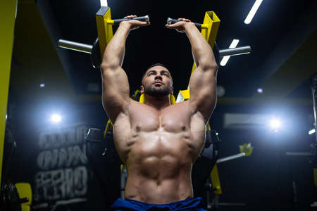 Front view close up of a very strong and muscular athlete doing exercises in hammer strength machine in a gym