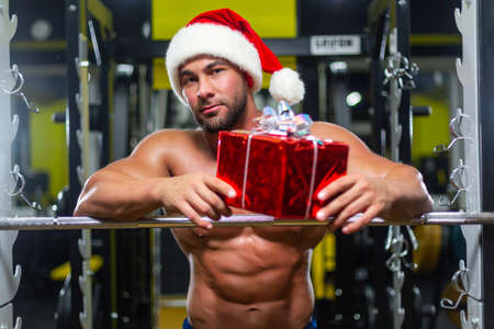 Young muscular attractive Santa Claus in Christmas hat is holding a gift leaning on a barbell in a gym, front view
