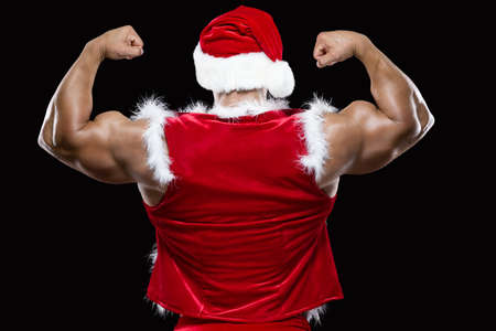 Back view of young Santa Claus in a red Christmas hat showing off his strong biceps isolated on black background Stock Photo