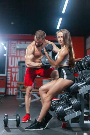 Muscular fitness man and woman bodybuilders are posing holding dumbbells near dumbbell shelf rack in modern gym