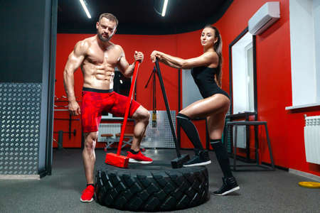 Full length portrait of muscular strong man and sexy fitness woman posing with sledgehammers and a tire in the gym