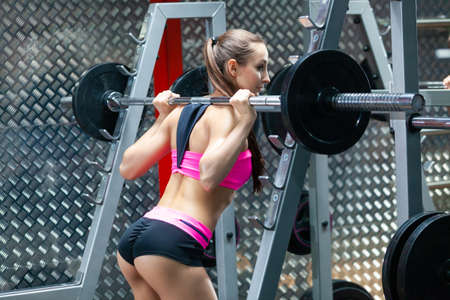 Back view of muscular girl with sexy buttocks performing squat exercises with a barbell in modern gym wearing pink and black sportswear