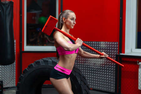 Side view of a muscular fitness woman posing near tire with sledgehammer on her shoulder in a modern gym