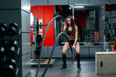 Full length photo of attractive young muscular girl using training ropes for battle ropes exercise in a gym 免版税图像