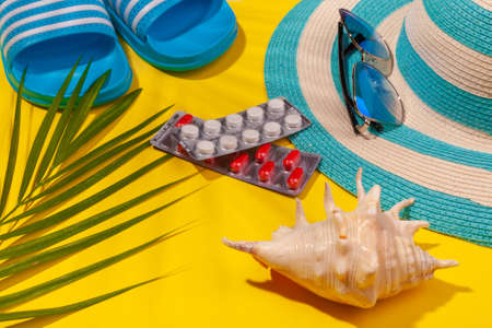 Top view on white and red pills in blister pack, blue hat, blue flip-flops, sunglasses, seashell, palm leaf on yellow background. Concept of beach holiday, sea tour, warm sunny summer. Acclimatization, illness during travel, health insurance.
