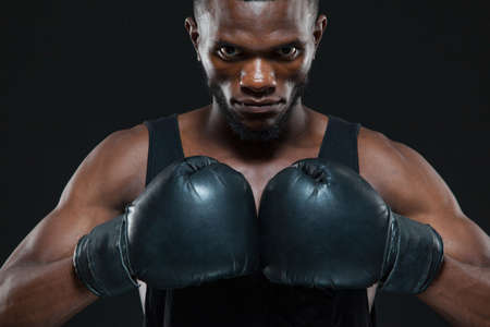 Front view shot of young African American boxer wearing gloves is posing isolated on a dark background