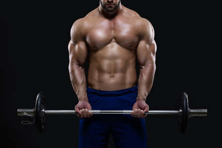 Handsome fitness man is standing with a heavy barbell ready to workout isolated on black background Фото со стока