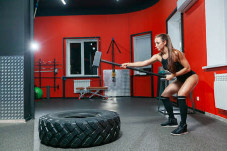 Full length portrait of sporty strong muscular girl training with sledgehammer in the modern gym