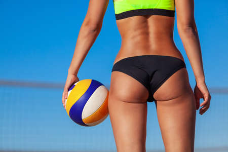Close-up of a volleyball ball and the butt of a beautiful girl in a bathing suit on the beach