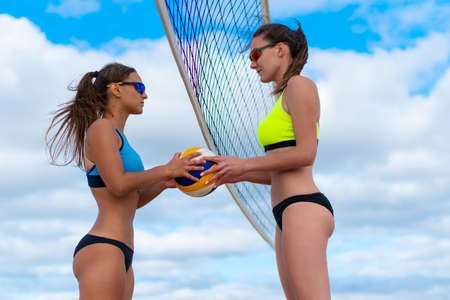 A girl in a yellow bathing suit passes a volleyball into the hands of a girl in a blue bathing suit on the beach