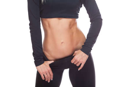 Close up of the muscular abdomen of a female athlete isolated on white background