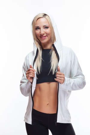 Slender athletic blonde with bare abs stands in a hood isolated on white background Stok Fotoğraf