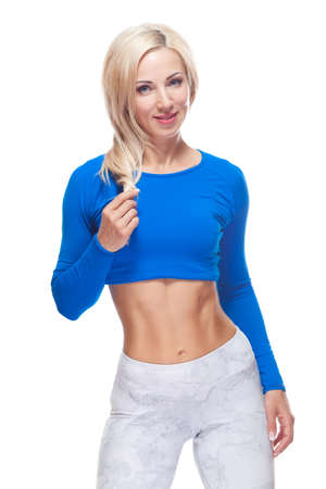Smiling young woman is standing with naked abs looking at camera isolated on white background Stok Fotoğraf