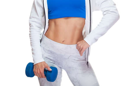 Close-up of muscular abs and a blue dumbbell in the hand of a young athletic girl isolated on white background