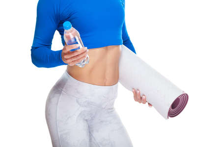 Close up shot of attractive sportswoman abs with a bottle of mineral water and a mat in her hands isolated on white background