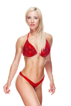 Sexy blond bodybuilder woman in red bikini is posing and showing muscle isolated on white background