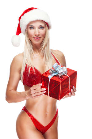 Bodybuilder blonde woman wearing a red bathing suit, wearing a Santa hat, is standing holding a present isolated on white background