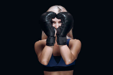 A sporty blonde in boxing gloves holds her hands in front of her face smiles and prepares for training isolated on black background In the shape of a heart. Stok Fotoğraf