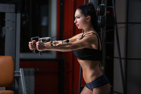 Side view of sporty brunette girl in sportswear working out and training her arms and shoulders in crossover in gym