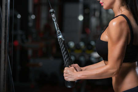 Close up of strong muscular arms of young woman doing exercise on the triceps in the crossover in the gym