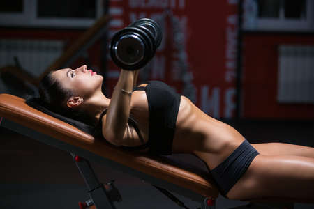 Athletic young woman brunette in sportswear is doing a dumbbell press on inclined bench at gym Stok Fotoğraf