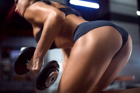 Beautiful view of sexy sporty buttocks of athlete woman in sportswear training back with dumbbell in one hand leaning on the bench at fitness gym