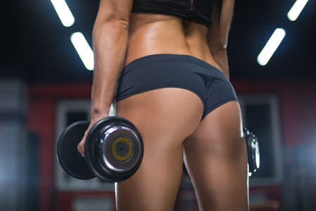 Close up view sexy sporty buttocks of athlete girl holding dumbbells in a gym Stok Fotoğraf