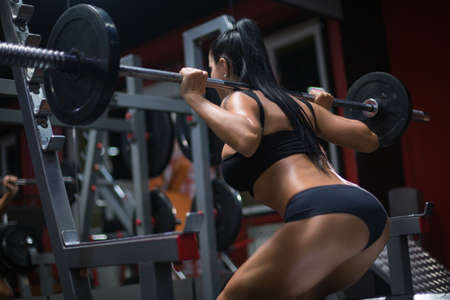 Back view of beautiful sporty woman doing squats with a barbell working out in gym