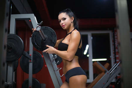 Beautiful sporty sexy woman is posing near a barbell after training looking at camera in gym Stok Fotoğraf