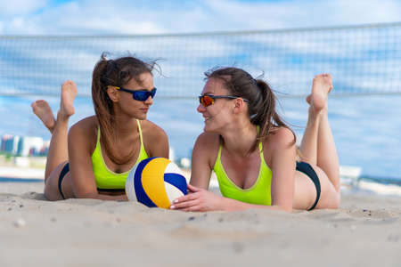Portrait of two smiling female beach volleyball players in sunglasses lying on sand with a ball on the background of the net. Summer vacation and sport concept 免版税图像