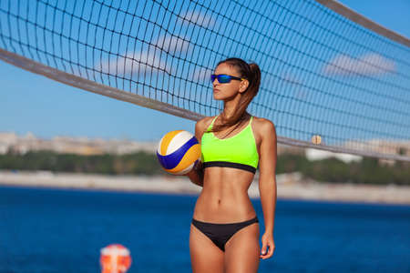 Sexy slender brunette in a bright swimsuit and sunglasses poses with a ball on the beach near the beach volleyball net