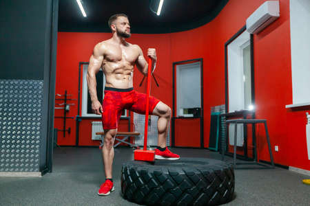 Full length portrait of sporty muscular man posing with sledgehammer and tire in the gym ready to exercise