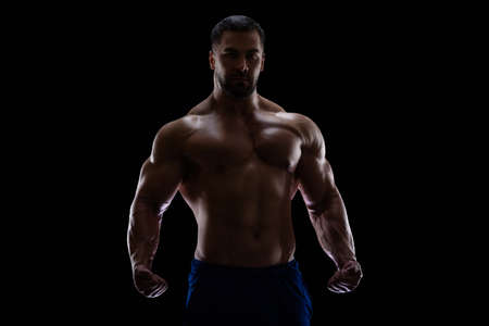Portrait of a bodybuilder standing isolated on black background in a shadow with clenched fists to show off his muscles