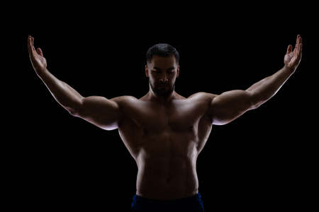 Portrait of a bodybuilder standing isolated on black background in a shadow with raised hands to show off his muscles