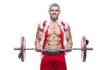 Sexy Santa Claus. Bodybuilder young handsome santa clause smile train muscles arms and biceps at New Years eve and Christmas winter holiday white background. Stock Photo