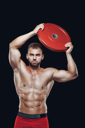 Portrait of sexy muscular male with a barbell disc raised above his head isolated on black background