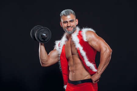 Sexy Santa Claus. Bodybuilder young handsome santa clause smile holds a dumbbells and shows off abs cubes at New Years eve and Christmas winter holiday black background.