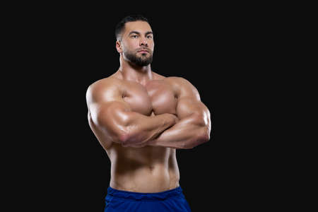 Strong athlete man is standing with hands folded on his chest looking at camera isolated on black background Фото со стока