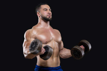 Young muscular sportsman is lifting heavy dumbbells showing his strong biceps isolated on black backgrounds