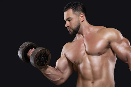 A handsome beefy man is focused on performing the exercise lifting a dumbbell with one hand isolated on black background 版權商用圖片